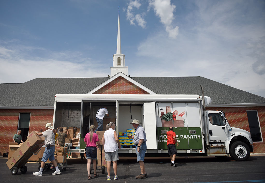 Volunteers at the Ashland Baptist Church unload food delivered by the Food Bank truck