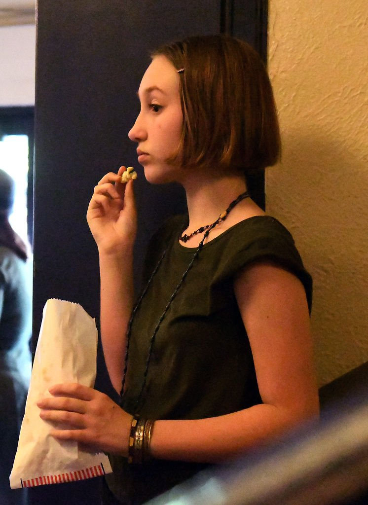 Vivian Harrison, 12, snacks on popcorn