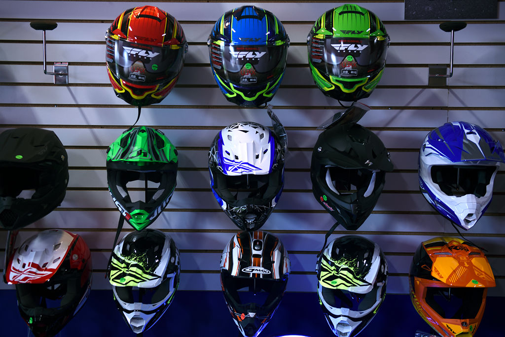 Helmets for sale are hung on display at F&A Cycle