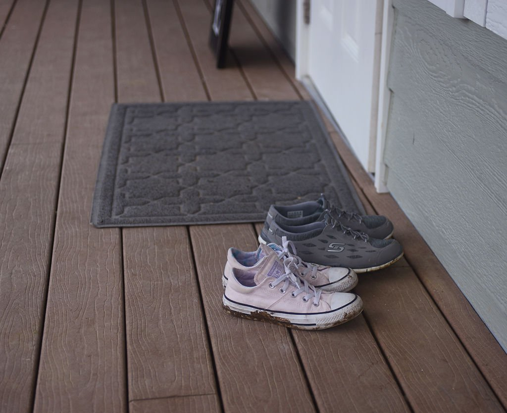 Shoes wait for their wearers outside of the Petersheim Home