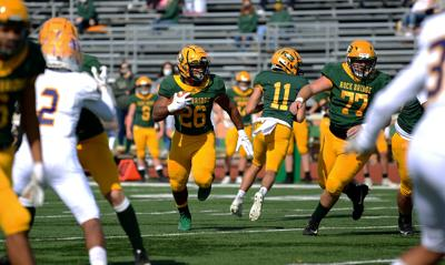 Rock Bridge senior running back Bryce Jackson runs with the ball through the offensive line, after receiving a hand pass by junior quarterback Nathan Dent