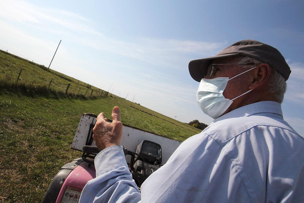 "Robert ""Doc"" Kinkead rides a four wheeler through his pasture"