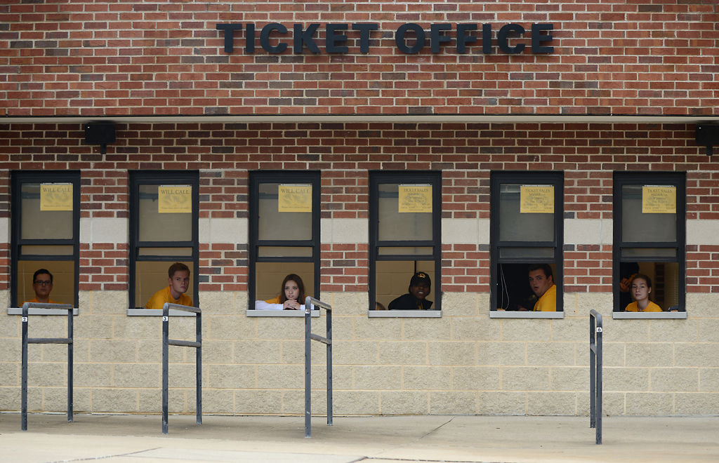 Employees working the ticket booths at Memorial Stadium watch a K9 Unit unload before the game