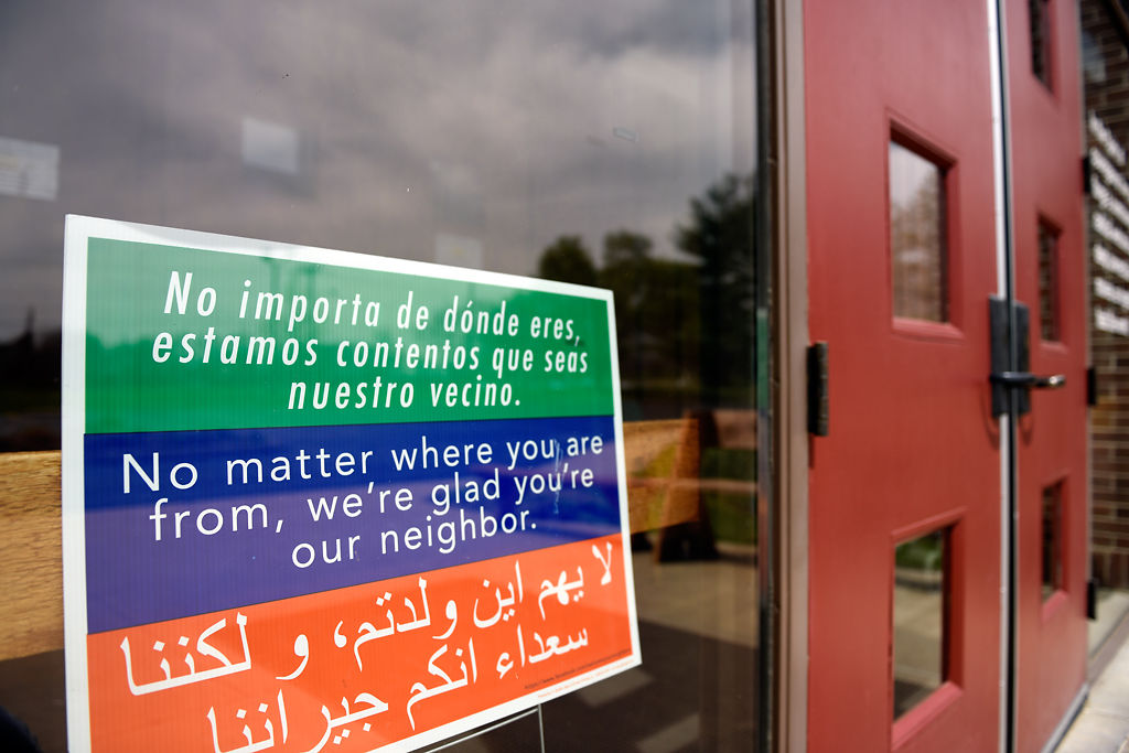 A sign welcoming visitors sits in the window