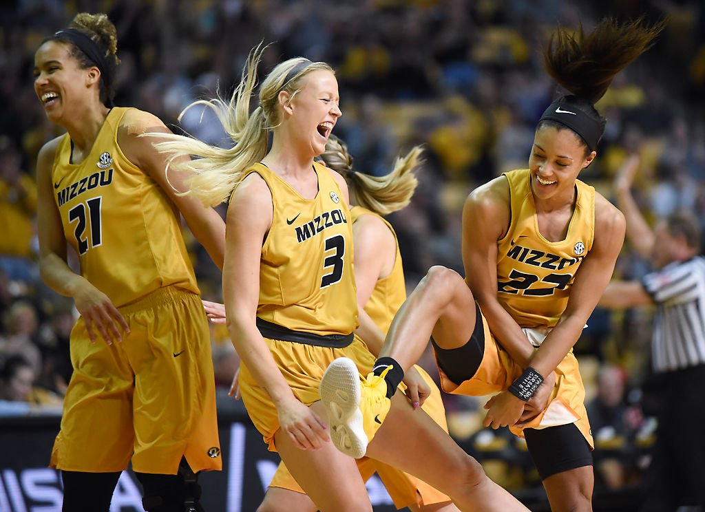 Tiger teammates jump in celebration of a three-point basket