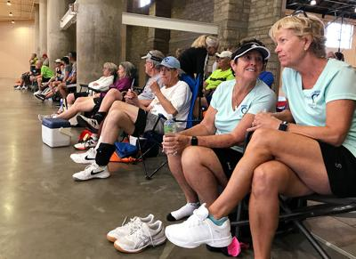 Pickleball teammates Susie Burton, left, and Nancy Scanlan rest alongside the courts