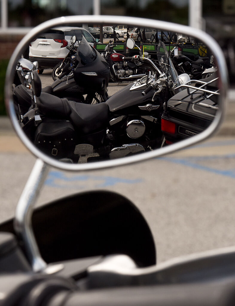 An array of motorcycles are seen in the rearview mirror of a motorcycle