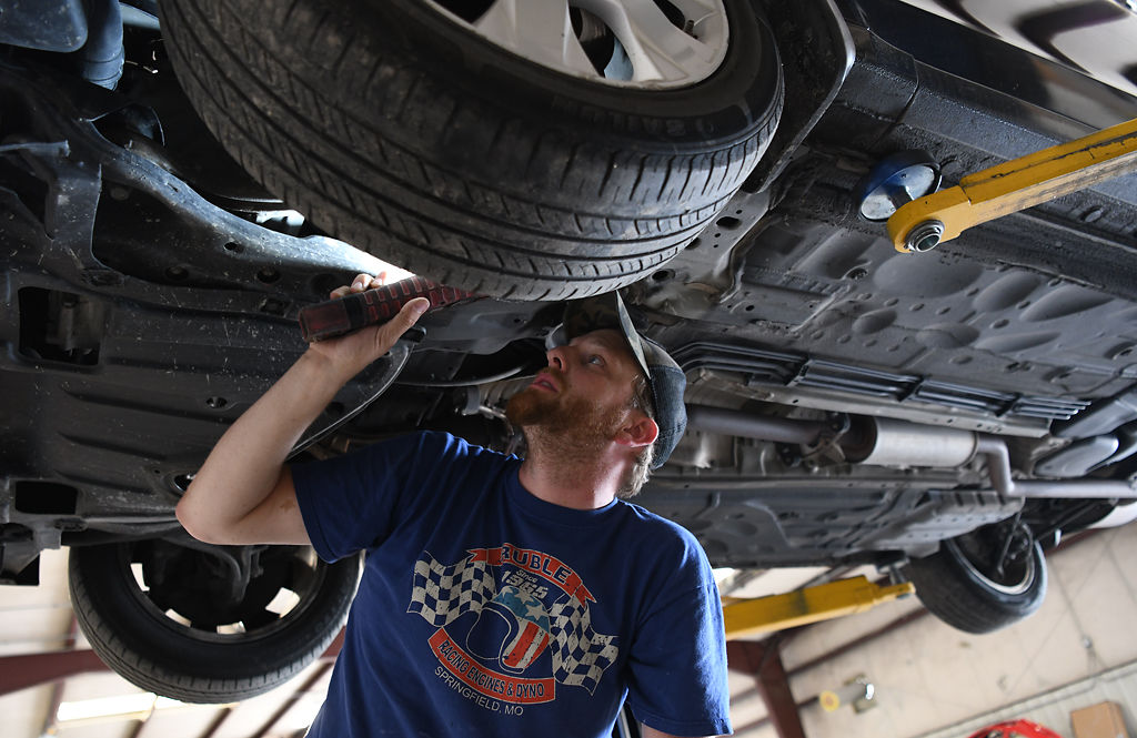 Galen Hassler checks the suspension on a customer's car