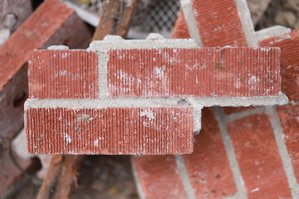 Red brick scatters across the rubble