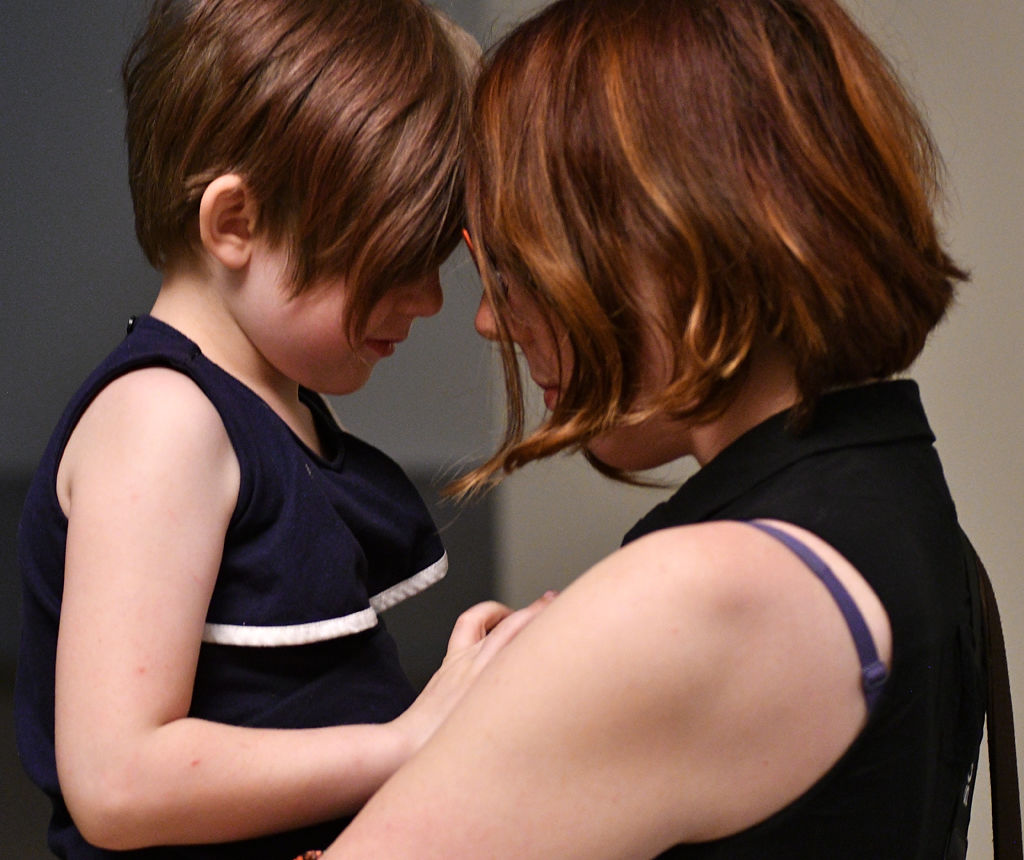 Charlotte Monroe, 5, and her mother Renee Brochu embrace in state Capitol