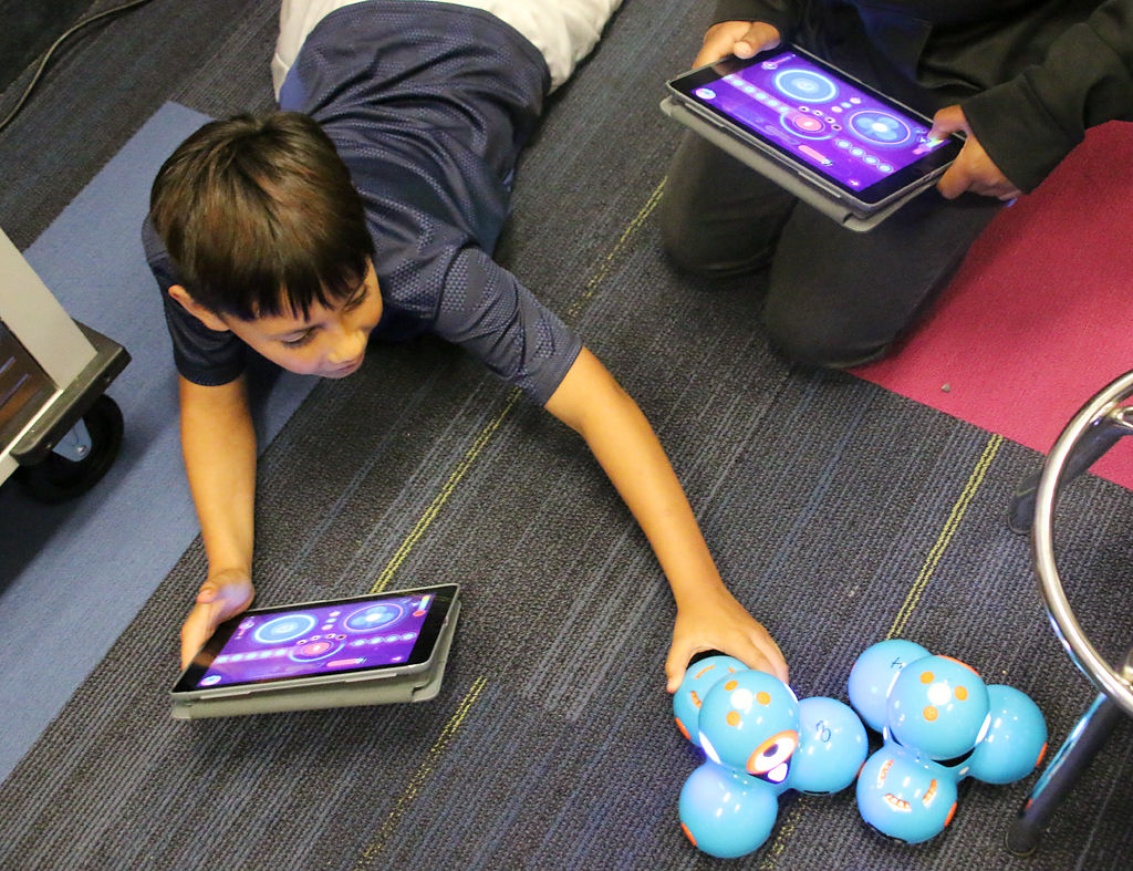 Fifth-graders Cristian Moreno and John Ward use iPads to battle each other