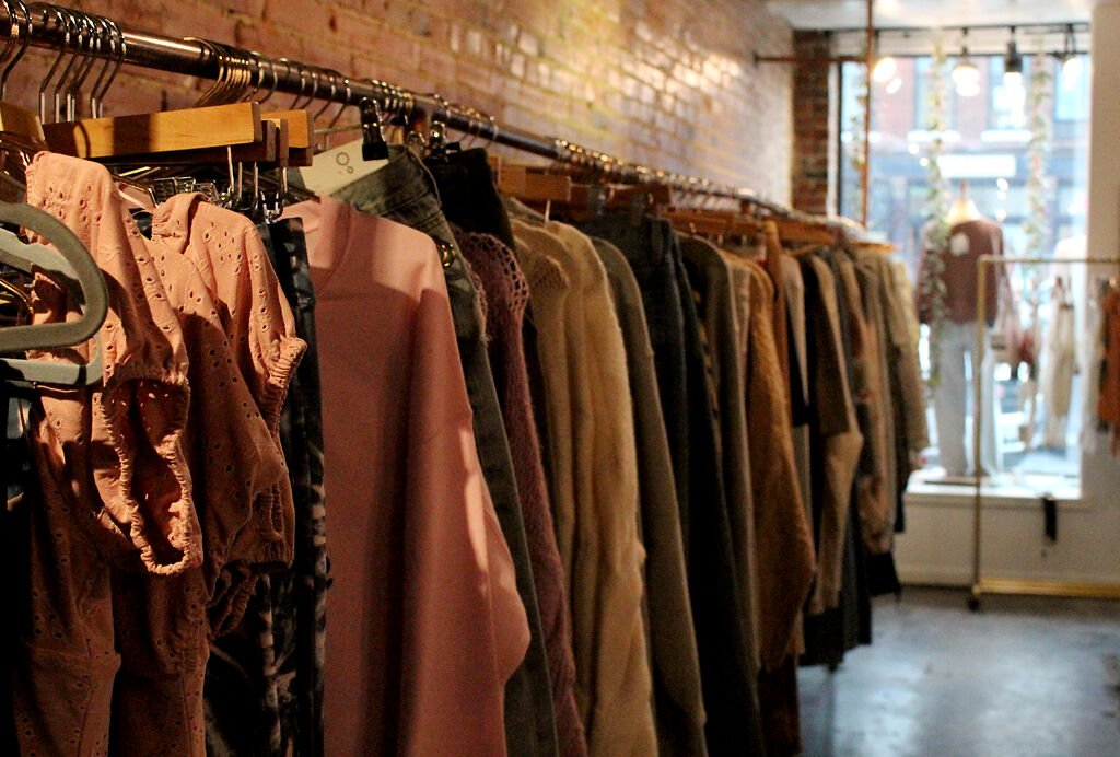 A row of clothes hangs on the rack