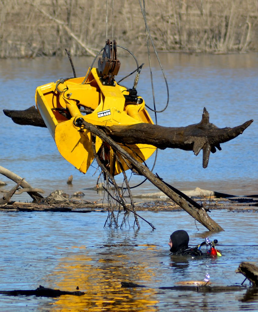 An excavator picks up debris from the bottom of Lamine River