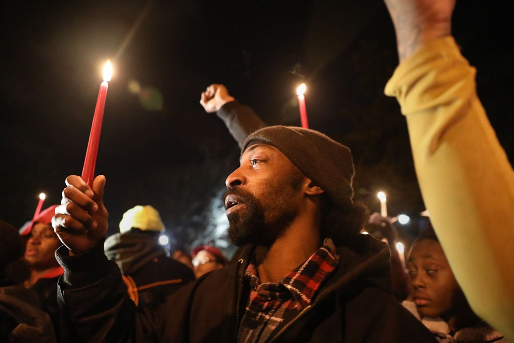 Kenneth Harris-Jones, a cousin of Ahmonta Harris, holds a lit candle