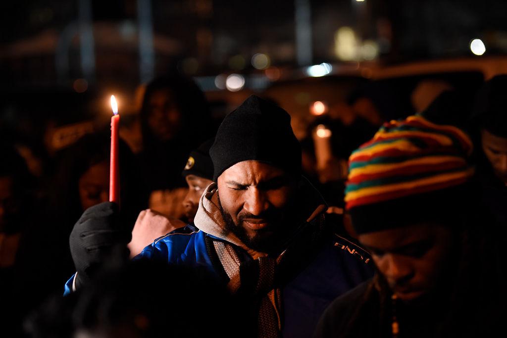 James Glenn, father of Ahmonta Harris, prays with vigil attendees
