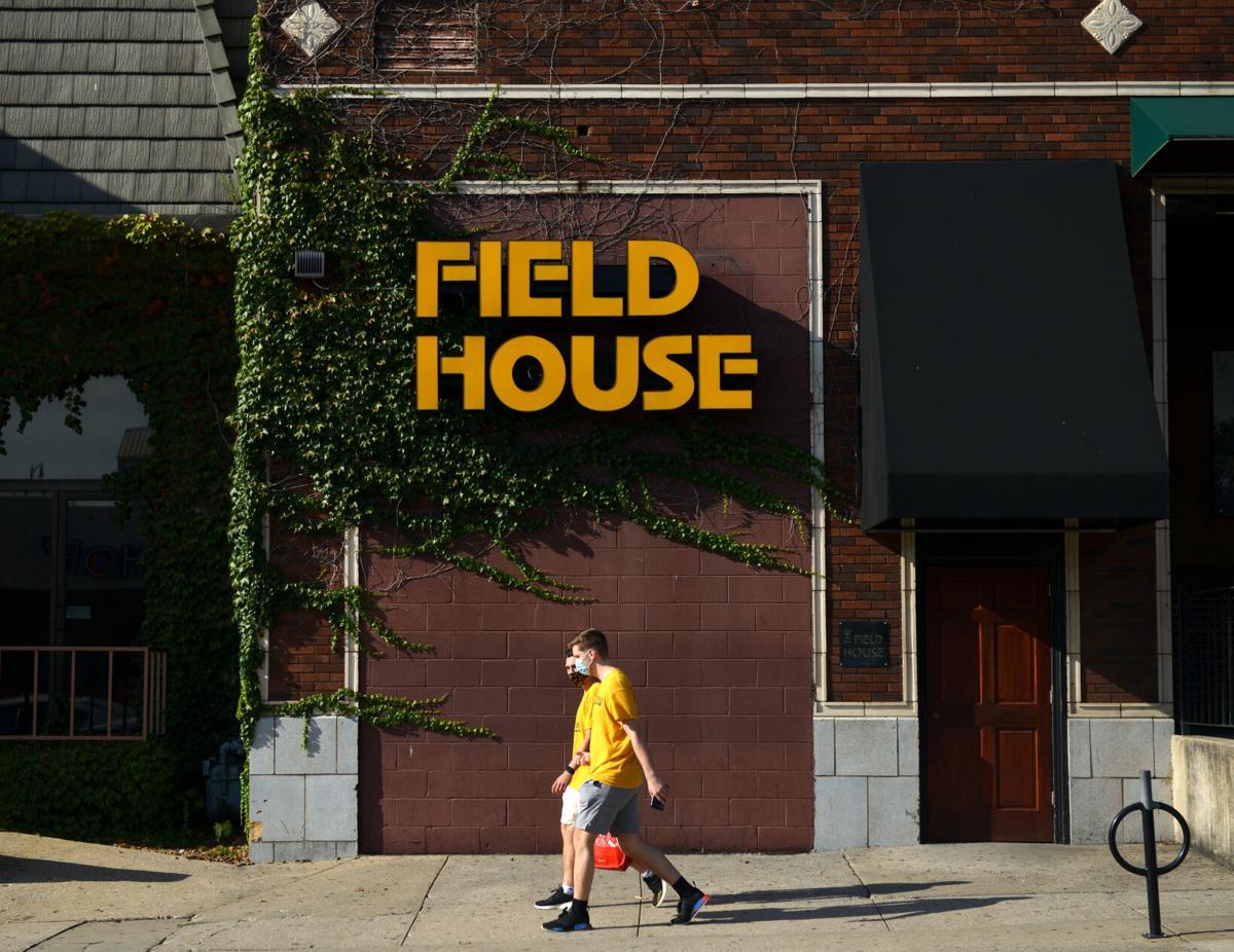 Pedestrians walk by Field House bar