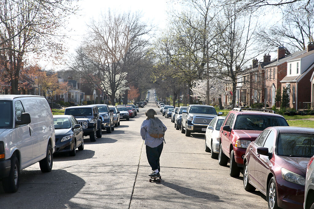 Miles longboards down a neighborhood street