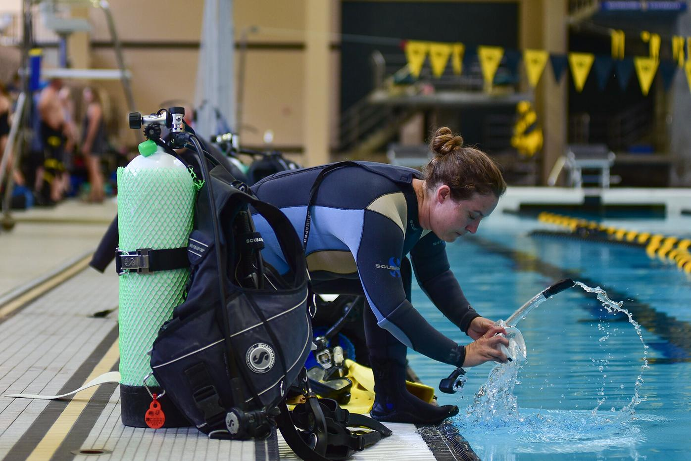 Fulton resident Amy Sue Guinn cleans off her dive mask before entering the pool for a scuba diving class