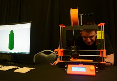 Konnar Jones watches his 3D printer on Saturday at Parkade Plaza. Jones was the receiver of the 2019 Young Entrepreneur Award