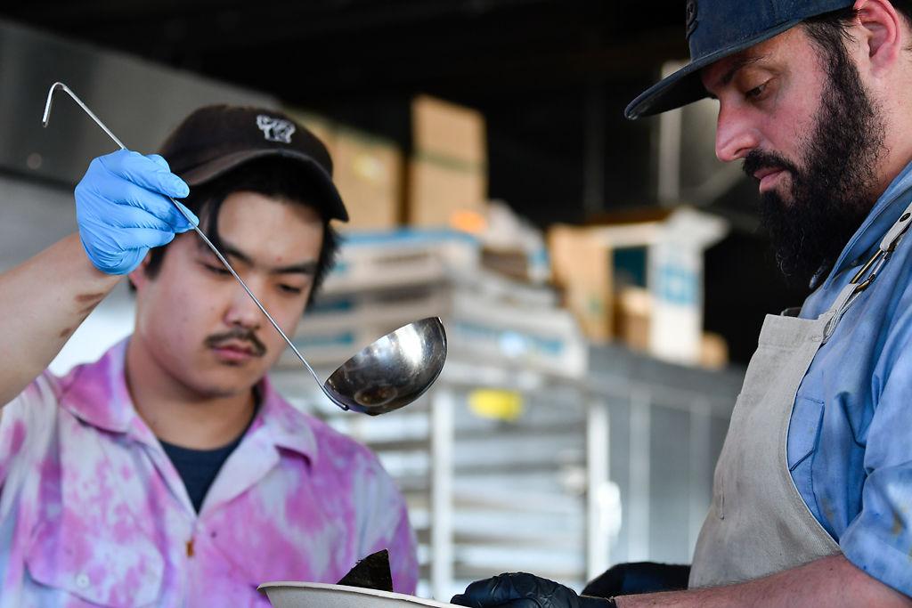 Vinnie Debono, left, and Benjamin Hamrah finish preparing a bowl of udon noodles