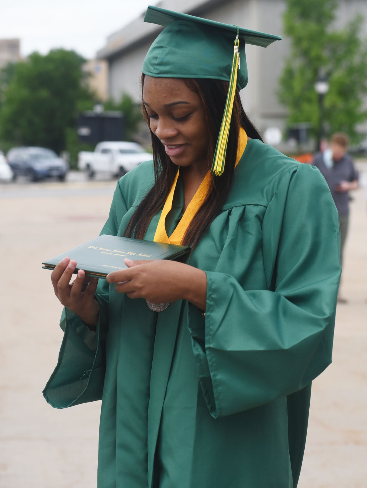 Aris Collier holds her diploma