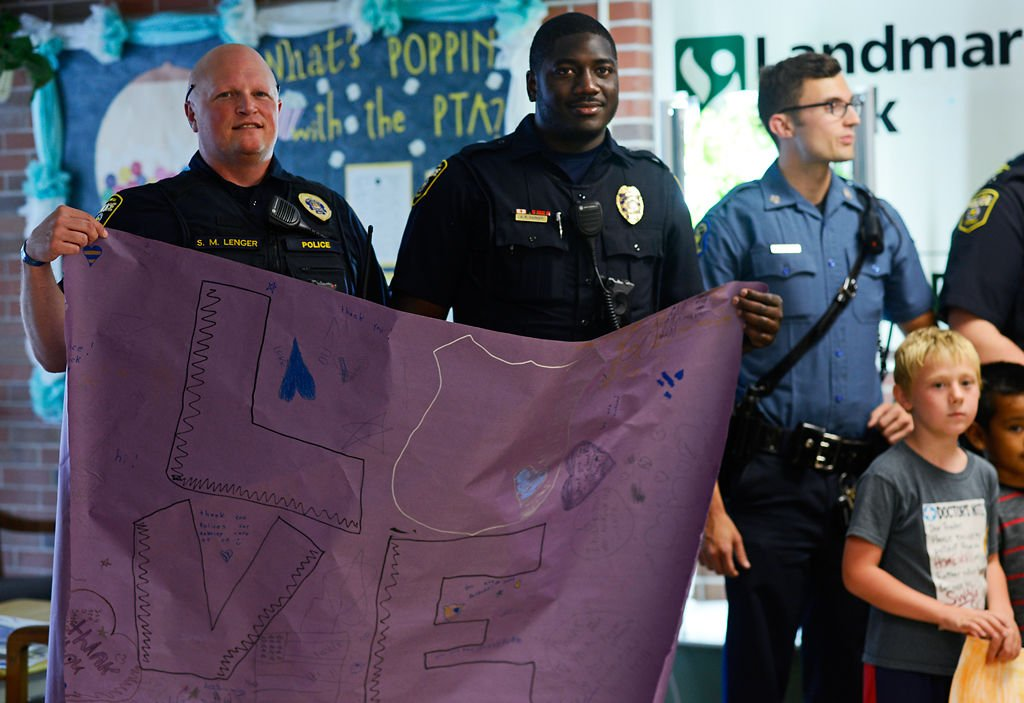 Sgt. Scott Lenger and Officer Tony Parker hold up the sign