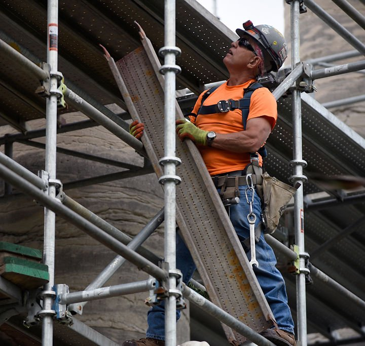 Kenny Saale hoists scaffolding parts to a coworker