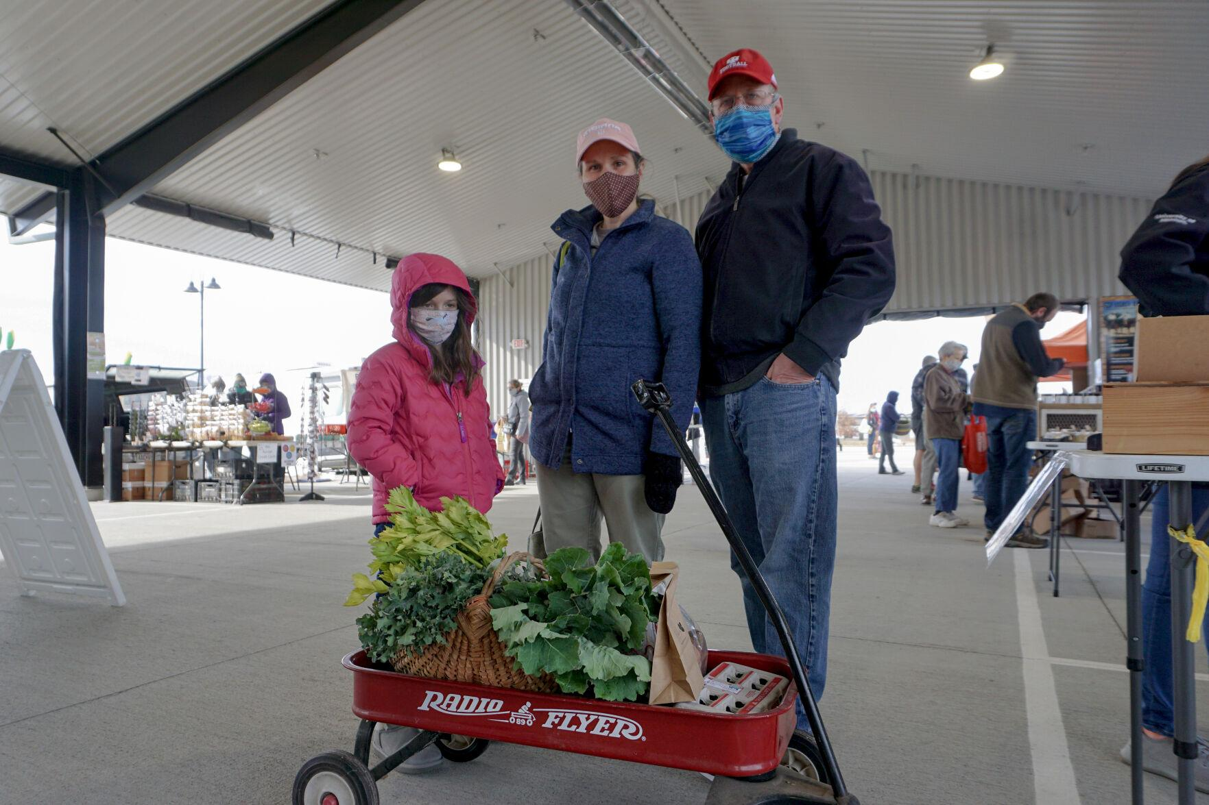 Carlann and her parents stand with their radio flyer wagon of groceries