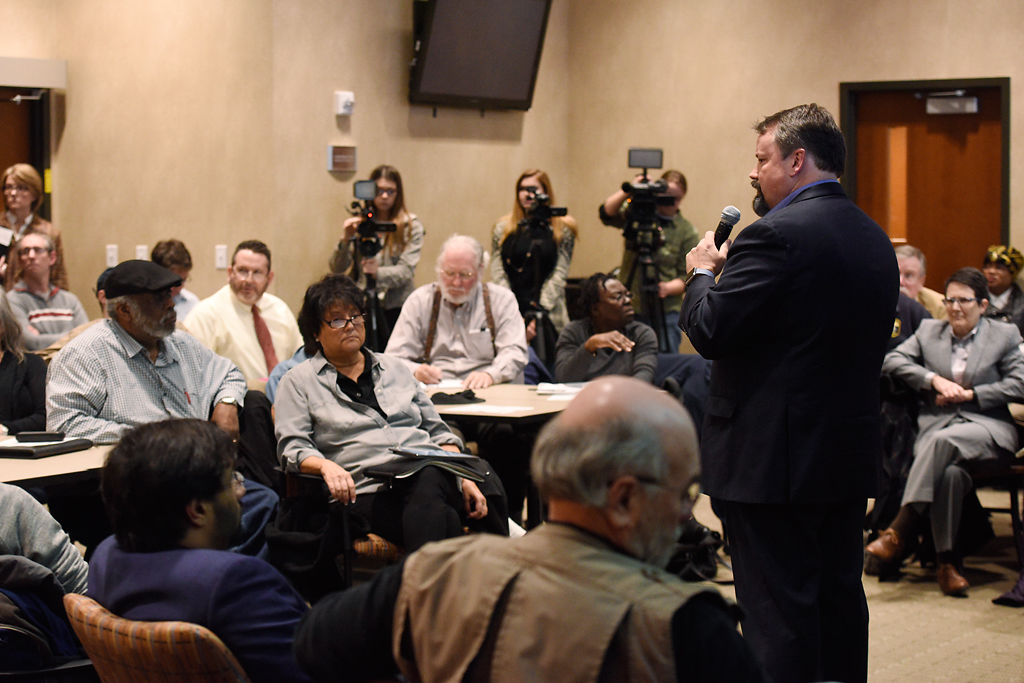 City Manager talks to the audience during a town hall meeting on racial profiling