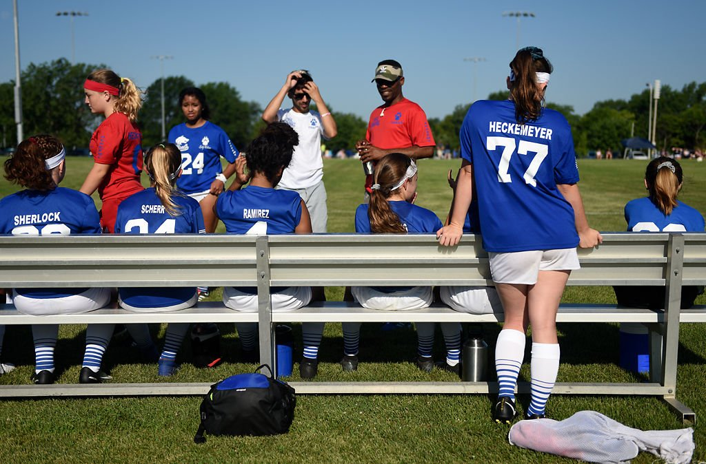 Players from the Lady Wolves of Ashland sit on the bench