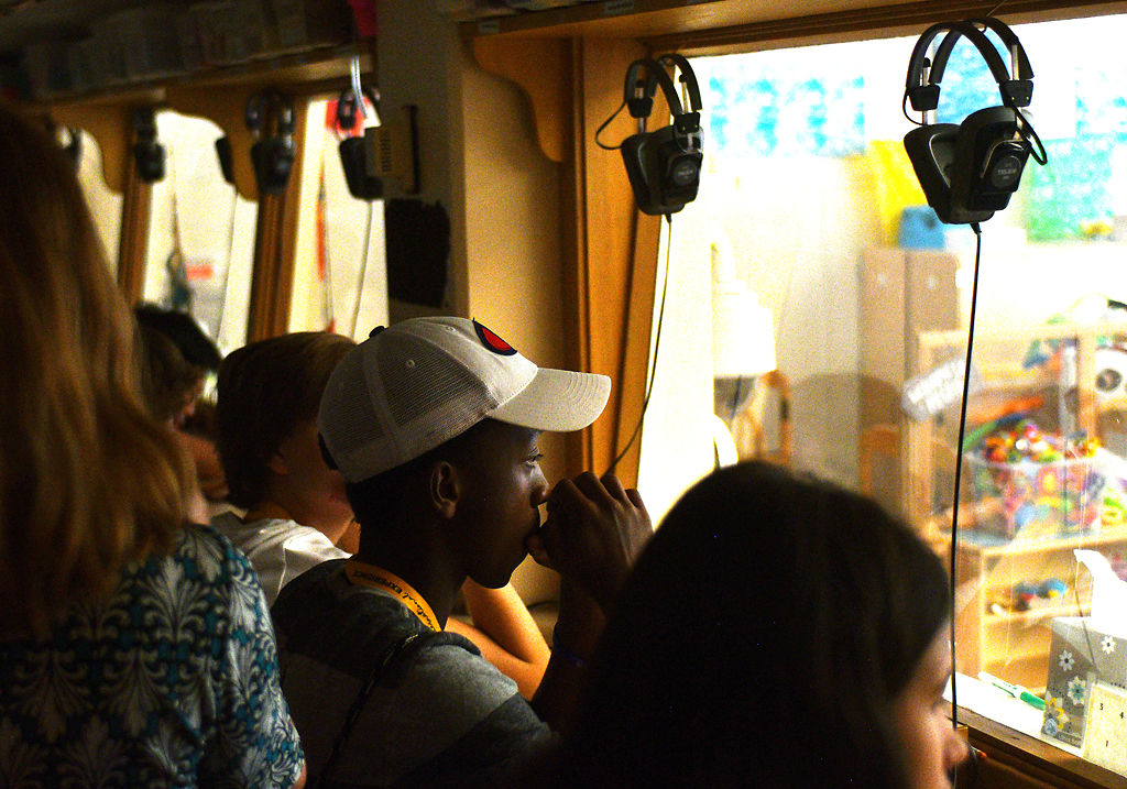 Student Emile Ndabarishe, center, from the Mizzou International Education Program watches kids play through a one-way mirror