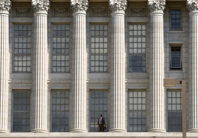 A man stands between columns at the Missouri Capitol