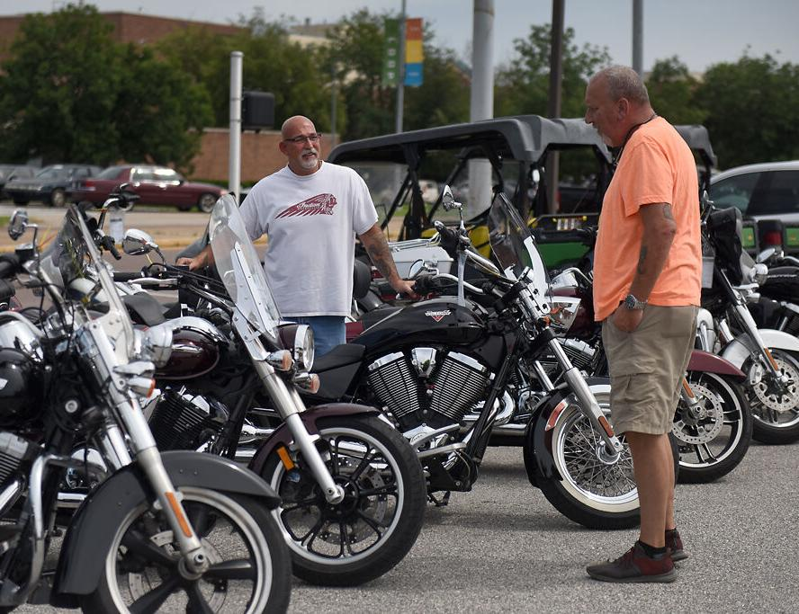 Indian Motorcycle employee Eric Myers, left, talks to Cole Robbins