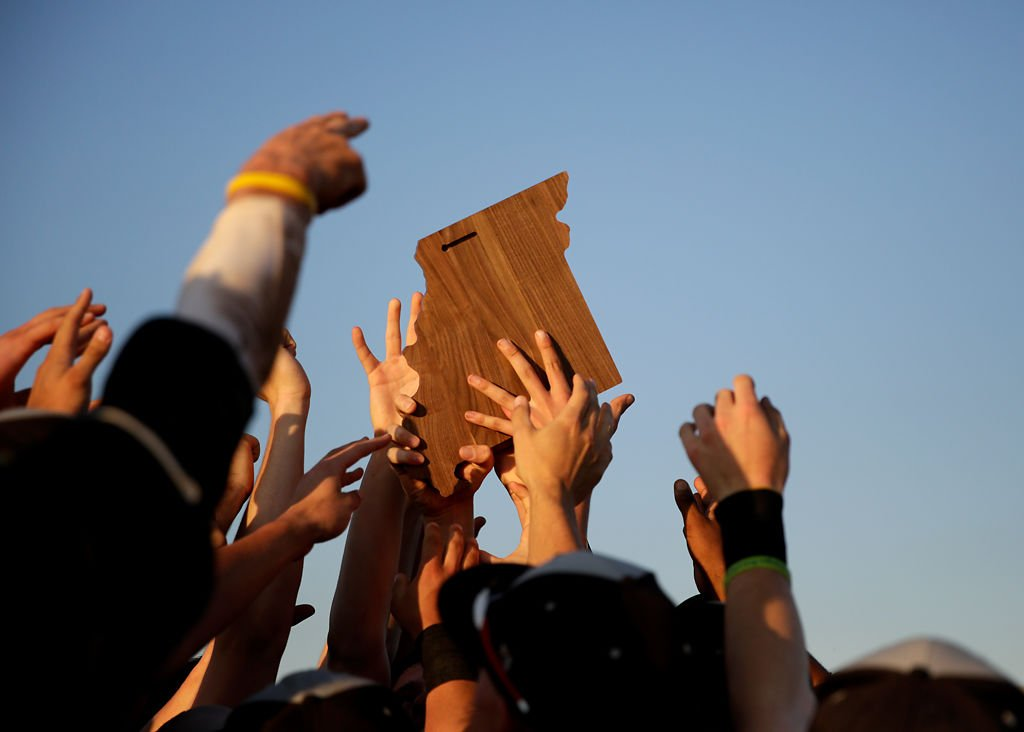 Hoisting the district trophy, Rock Bridge baseball players celebrate at midfield together