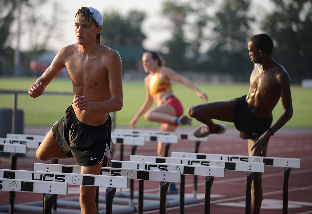 Missouri cross country runners practice with hurdles