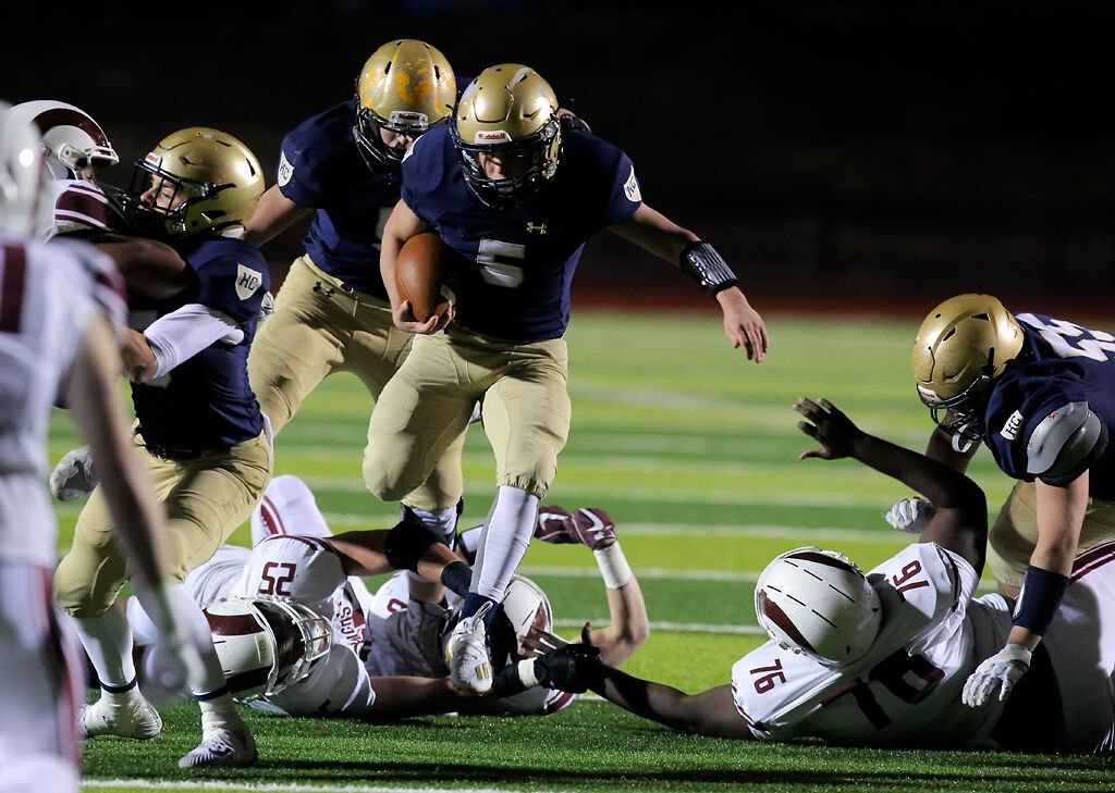 Helias senior running back Alex Clement runs through the MICDS defensive line at the Class 4 championship game of the Show-Me Bowl at Adkins Stadium