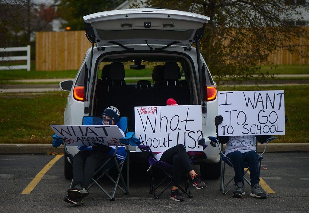 Harrison Moyers, Annika Lindenbusch and Hayden Moyers hold signs