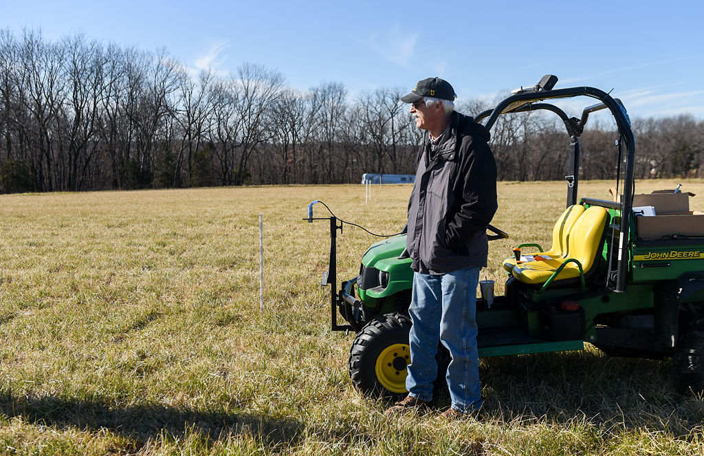 Gene Schmitz stands near a test plot of land