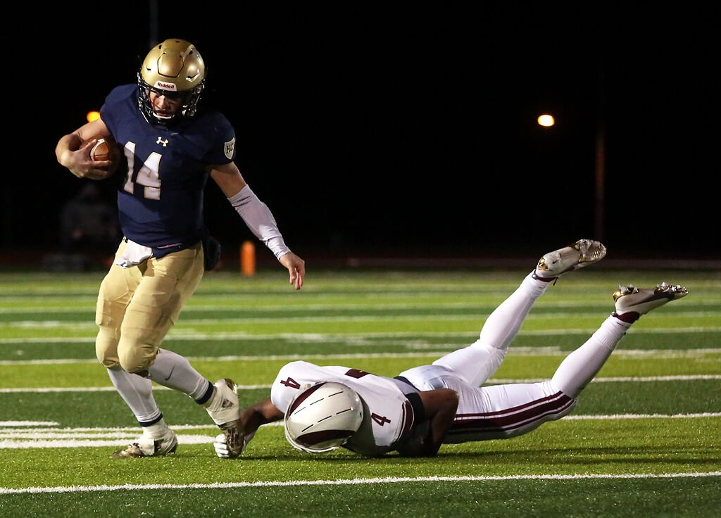 Helias senior quarterback Jacob Weaver avoids a sack by MICDS senior linebacker Jalen Pace at the Class 4 championship game of the Show-Me Bowl at Adkins Stadium