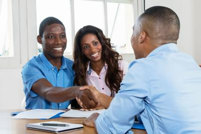 couple shaking hands with bank or real estate deal