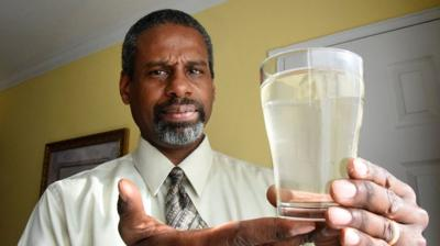 drinking water unsafe kansas man holds glass