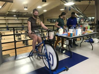Student rides a stationary bike for a free smoothie