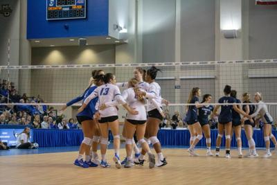 Volleyball groups after winning point against Xavier