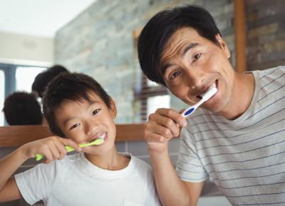 Dad and son brushing their teeth
