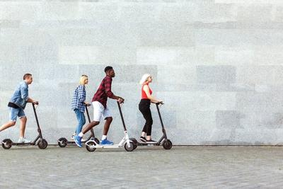 Company,Of,Friends,Rides,Electric,Scooters,Against,The,Background