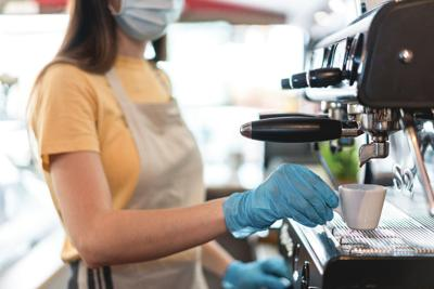 Young,Female,Working,Inside,Bar,Restaurant,While,Making,Coffee,Wearing