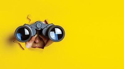 Female,Hand,Holds,Black,Binoculars,On,A,Yellow,Background.,Journey,
