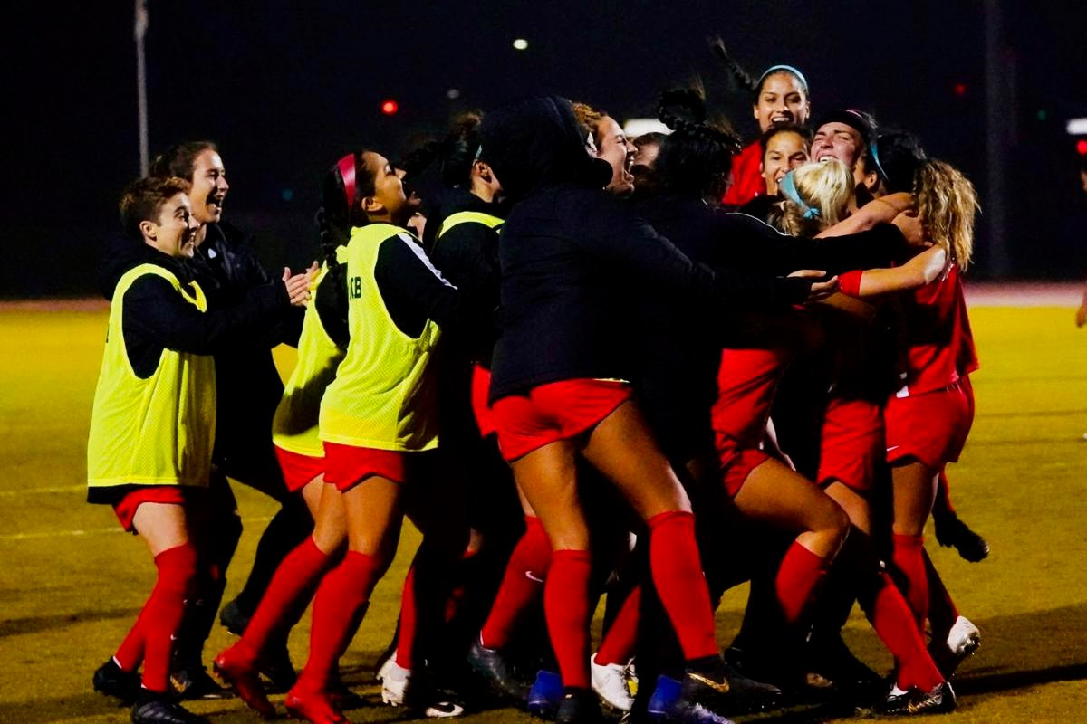Women's Soccer Team celebrating the overtime goal to win the game.