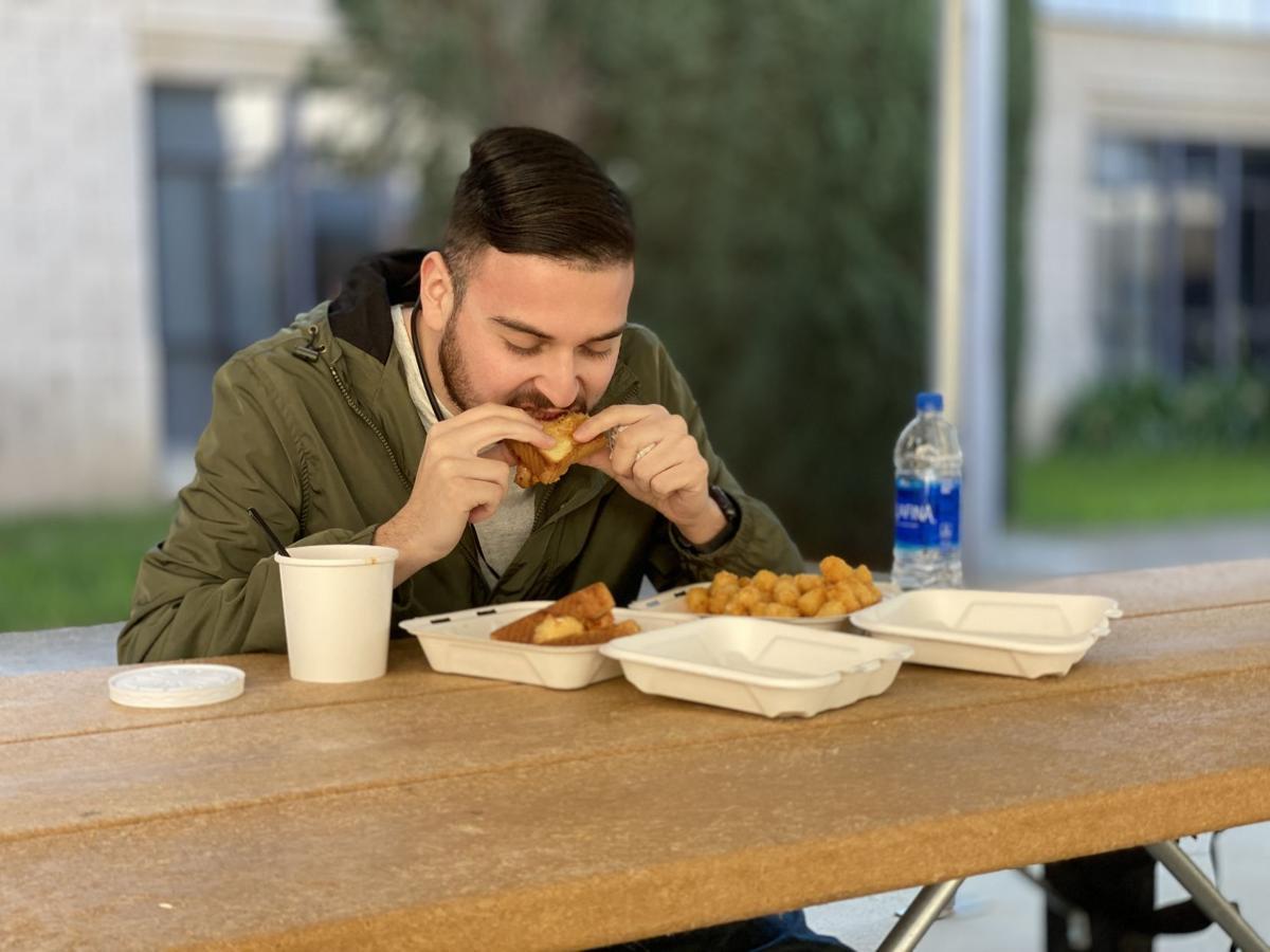 """Anthony Ramirez (senior, History) eating an """"Old Glory"""" sandwich"""