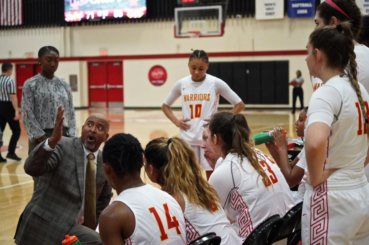 Women Basketball Players listening to Head Coach Wayman Strickland